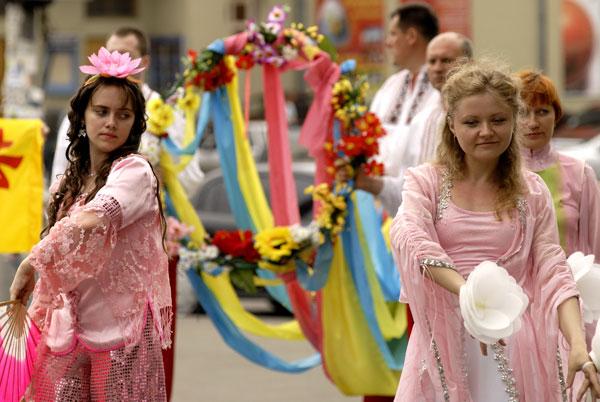 Дівчата танцюють із віялами й лотосами під час параду послідовників Фалуньгун у Києві 8 липня 2008 року. Фото: The Epoch Times