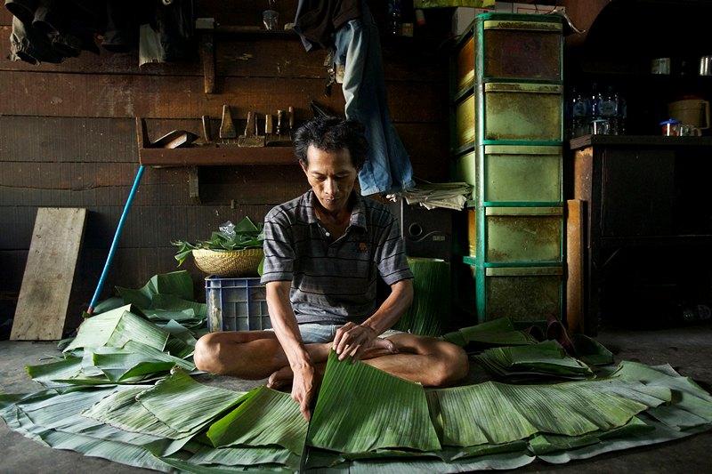 Джакарта, Индонезия, 12 июля. Рабочий небольшой фабрики нарезает листья банана, которые используются как упаковка для готовой еды. Фото: Ed Wray/Getty Images