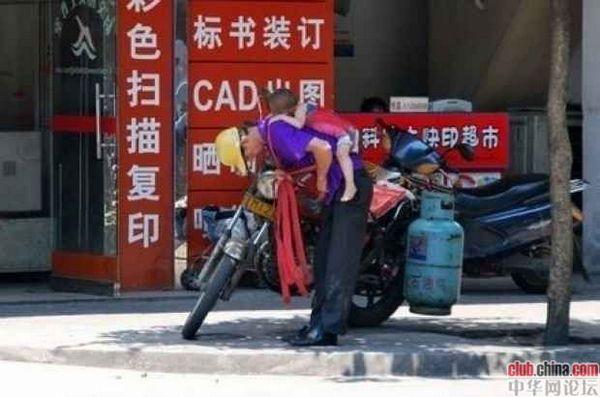 Рабочий по доставке газовых баллонов из города Фошань провинции Гуандун по фамилии Ли. Его жена до позднего вечера работает на швейной фабрике, поэтому он вынужден целый день возить с собой маленького сынишку, привязав его к спине. Фото с aboluowang.com