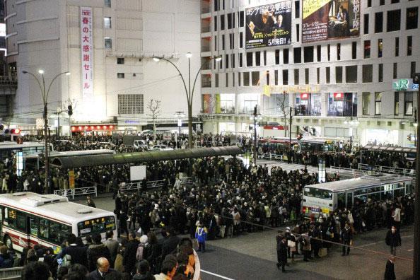 Сотни людей ждут автобусов на автостанции Токио после того, как было остановлено движение пригородных поездов в районе Большого Токио после сильного землетрясения в Японии 11 марта 2011 года. Фото: AFP PHOTO / JIJI PRESS