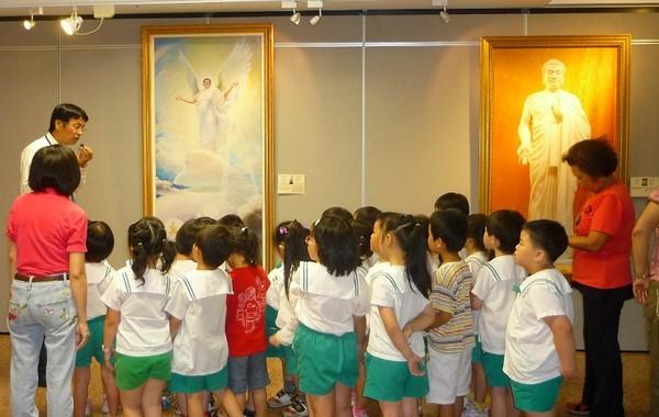 Вчителі та учні школи Синьонфу розглядають картини