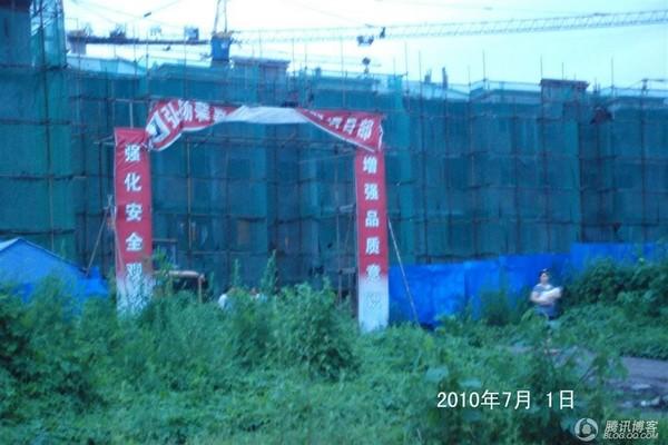 Селище, що споруджується. Одна з новобудов майбутнього селища зруйнувалася під час спорудження. На конструкції у вигляді арки написано гасло, під яким проходить будівництво «Зміцнимо поняття безпеки, посилимо усвідомлення поліпшення якості». Провінція Сич