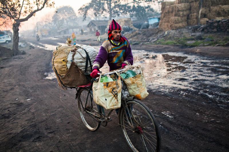Мужчина везёт на велосипеде уголь через посёлок Гуханвади. Фото: Daniel Berehulak/Getty Images