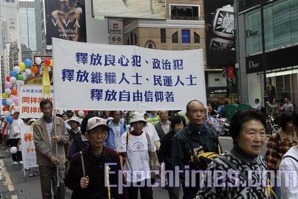 Гонконг. Шествие в поддержку Всемирной эстафеты факела в защиту прав человека. Надпись на плакате: «Освободить узников совести, полит заключённых и правозащитников». Фото: Ли Чжунюань/ The Epoch Times