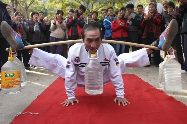 60-летний Вэн Ваньдэ держит груз весом около 30 кг. Фото с epochtimes.com
