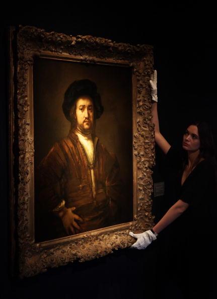 Работник «Кристиз» (Christie's) держит портрет кисти Рембрандта, который выставят на аукцион на следующей недели. Ожидаемая выручка от продажи полотна - от 18 до 25 млн фунтов стерлингов. Фото: Peter Macdiarmid/Getty Images