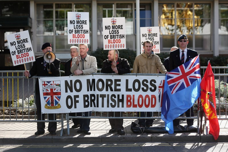 Бірмінгем, Англія, 7жовтня. Протестувальники стоять з плакатами біля будівлі, де проходить щорічний з'їзд правлячої партії консерваторів, виступаючи проти затримки виведення військ Великобританії з Афганістану. Фото: Oli Scarff/Getty Images