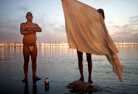 Паломник одевается после купания. Аллахабад. Индия.(20.01.2007) Фото: Mario Tama/Getty Images