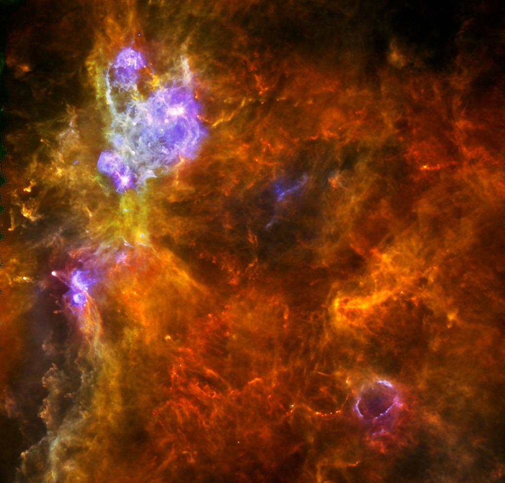 Молекулярное облако W3, отстоящее от нас на 6200 световых лет в рукаве Персея. Жёлтые точки в окружении красного вещества — будущие звёзды. Голубым цветом показан нагреваемый излучением молодых светил газ. Фото: ESA/PACS & SPIRE consortia
