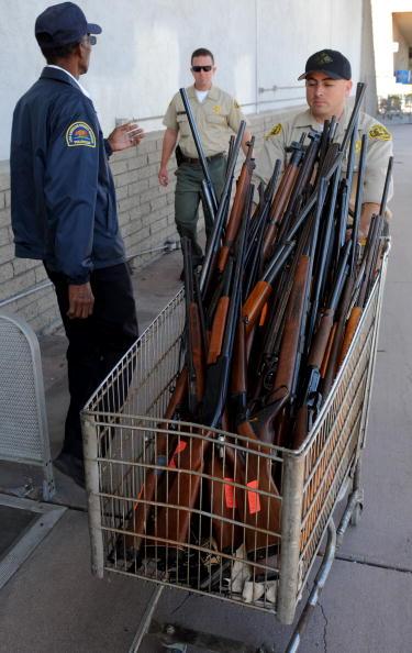 Полицейский везет винтовки, добровольно обмененные гражданами на деньги во время акции «Пистолет для подарочной карты». Это мероприятие проводится два раза в год: в День Матери и на Рождество. За каждую рабочую винтовку и пистолет можно получить подароч