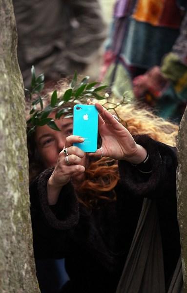 Учасниця свята робить знімки урочистості за допомогою iPhone. Фото: Matt Cardy/Getty Images