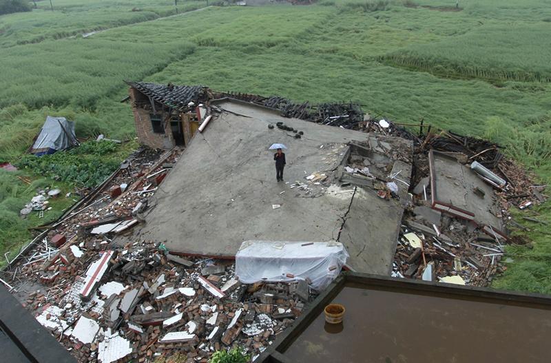 Лунмень, провінція Сичуань, Китай, 23 квітня. Жінка стоїть посеред руїн будинку в місті, що сильно постраждало від землетрусу. Фото: STR/AFP/Getty Images