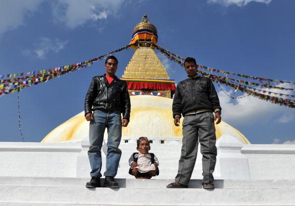 Найменша людина у світі на тлі ступи Будданатх в Непалі. Фото: PRAKASH MATHEMA/AFP/Getty Images
