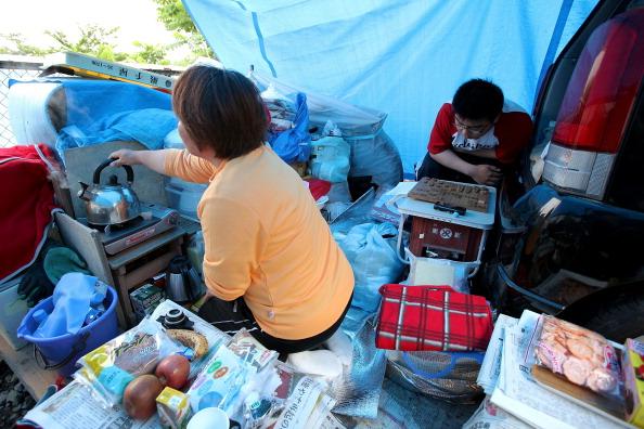 47-річна Сакік Ямагучі (ліворуч) із сином Мая Ямагучі спорудили тимчасове житло на парковці біля початкової школи Андо, що перетворилася на евакуаційний центр. м. Отсучі, префектура Івате. Фото: Kiyoshi Ota/Getty Images