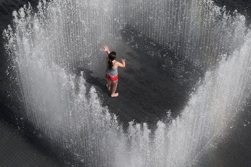 Лондон, Англія, 18 липня. Дівчинка грає у фонтані «Будинок з води», який створив данський дизайнер Джепп Хейн. У Британії вже другий тиждень дуже спекотно. Фото: Oli Scarff/Getty Images