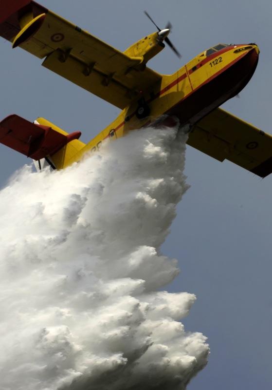 Водный бомбардировщик распыляет воду над лесом. Фото: MIGUEL RIOPA/AFP/Getty Images