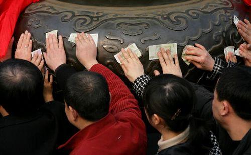 Храм Хуаен в г.Чунцзин (Китай). Люди прикладывают к бронзовой курильнице денежные банкноты, прося о счастье и благополучии. Фото: Getty Images