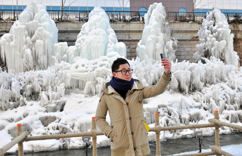 Сеул, Южная Корея, 3 января. Житель города делает снимок на фоне покрытых льдом деревьев. Температура в столице опустилась до –16,4 °С. Фото: JUNG YEON-JE/AFP/Getty Images