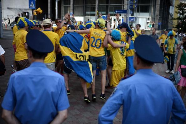 Шведские болельщики танцуют перед украинской милицией до матча Украины против Швеции 11 июня 2012 года. Фото: JEFF PACHOUD/AFP/GettyImages