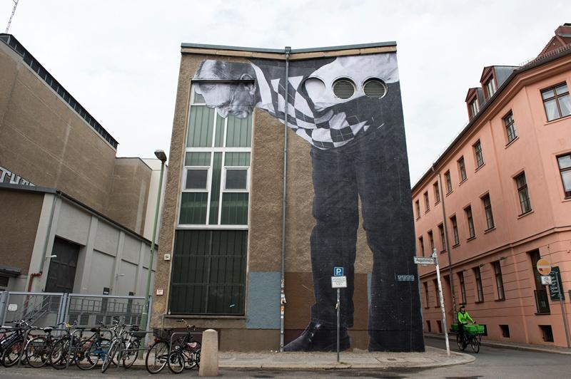 Берлін, Німеччина, 16 квітня. Французький фотограф JR у рамках проекту «Зморшки міста» розміщує на стінах фотографії літніх людей, які стали свідками історії міста. Фото: JOHN MACDOUGALL/AFP/Getty Images