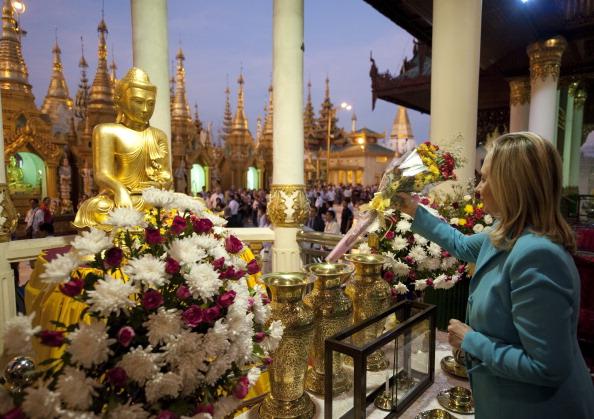 Держсекретар США Хілларі Клінтон залишає квіти перед статуєю Будди в буддійському храмі Шведагон в Янгоні. М'янма, 1 грудня 2011 року. Фото: Saul Loeb/Getty Images