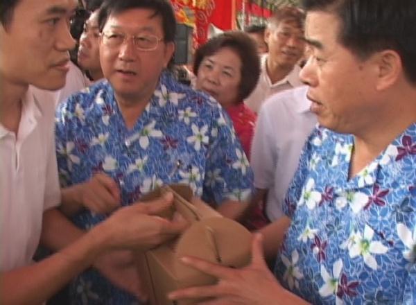 Мер провінції Гуандун Хуан Хуахуа відмовляється взяти у послідовника Фалуньгун матеріали зі звинуваченням його в геноциді. Фото: NTDTV