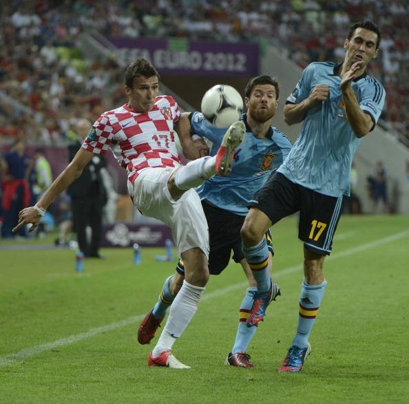 Хорват Маріо Манджукич (ліворуч) бореться за м'яч з Хабі Алонсо і Альваро Арбелоа (праворуч) з Іспанії під час матчу Хорватії проти Іспанії 18червня 2012,Арена Гданськ. Фото: PIERRE-PHILIPPE MARCOU/AFP/Getty Images
