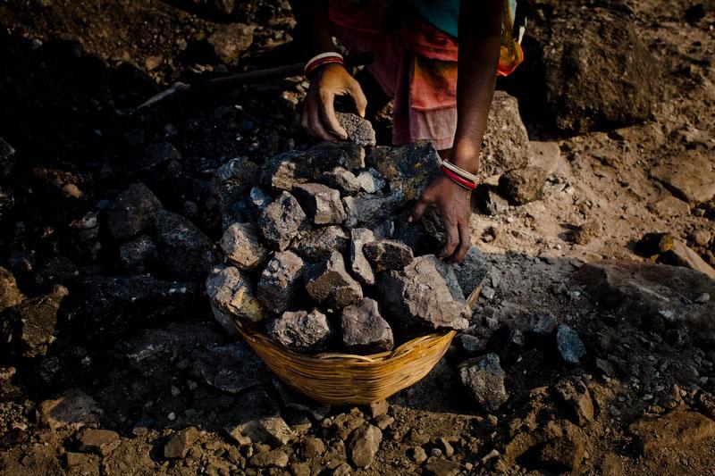 Жінка наповнює кошик вугіллям. Фото: Daniel Berehulak/Getty Images