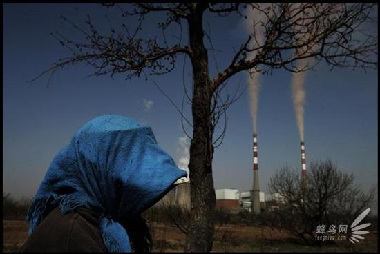 Місцеві жителі промислового району Хубінь міста Шісуйшен провінції Нінся, виходячи на вулицю, закутують голову і обличчя від часток пилу падаючих з димових труб місцевих підприємств. 22 квітня 2006. Фото: Лу Гуан