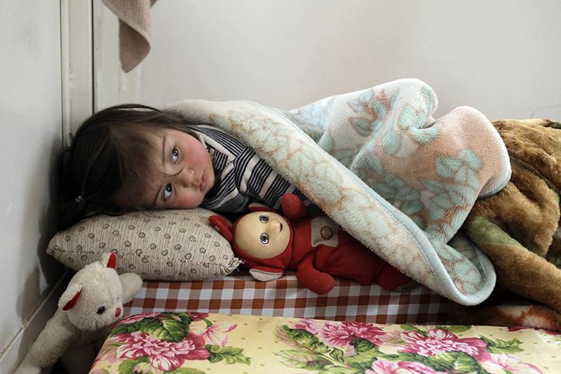 Сирийская девочка, бежавшая от насилия в Сирии лежит с куклой на кровати в лагере беженцев в ливанском городе Arsal в долине Бекаа 26 марта 2012 года. Фото: JOSEPH EID/AFP/Getty Images