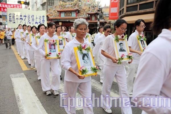 В белых траурных одеждах участники шествия несут фотографии погибших от репрессий в Китае сторонников Фалуньгун. 27 сентября. Тайвань. Фото: Тань Бинь/The Epoch Times