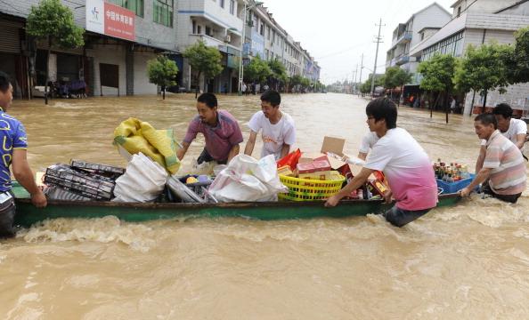 Китайцы перевозят свои вещи на лодке по воде после сильных дождей, обрушившихся на г. Ланси в восточной китайской провинции Чжэцзян. Фото: STR/AFP/Getty Images
