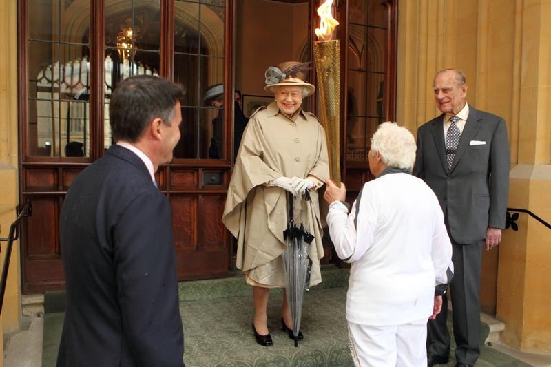 Виндзор, Англия, 10 июля. Олимпийский факел прибыл в Виндзорский замок. На фото: королева Елизавета II, принц Филипп (справа), лорд Себастьян Коэ (слева) и факелоносец Джина Макгрегор. Фото: Steve Parsons — WPA Pool/Getty Images