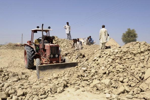 Пакистанцы убирают груды камня, в которые превратило землетрясение их дома. Фото: BANARAS KHAN/AFP/Getty Images
