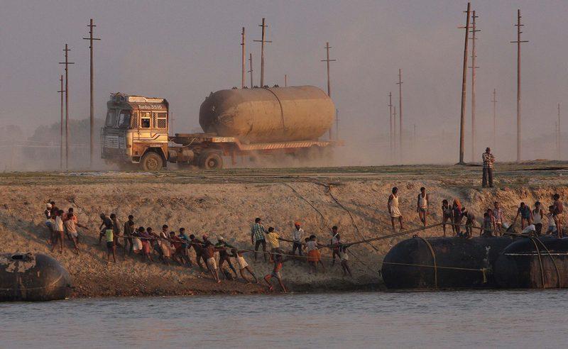 Аллахабад, Индия, 5 ноября. Местные жители строят понтонный мост через реку Ганг перед началом самого массового паломничества индусов к святыням. Обряд Кумбха-мела, или «Праздник кувшинов», проводится каждые 12 лет. Фото: STR/AFP/Getty Images