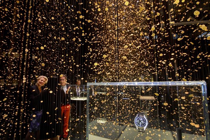 Базель, Швейцария, 25 апреля. Посетители крупнейшей в мире выставки часов любуются оформлением стенда фирмы Citizen «Гейзер времени», созданном из 50 тыс. часовых механизмов. Фото: FABRICE COFFRINI/AFP/Getty Images