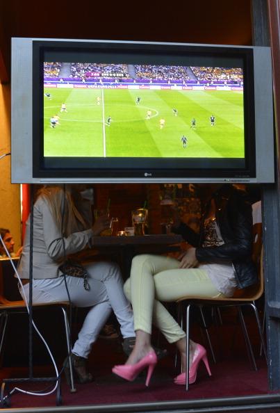 Дві жінки за телевізором, що показує матч Франції проти України 15 червня 2012 року в місті Вроцлав. Фото: ODD Andersen/AFP/Getty Images