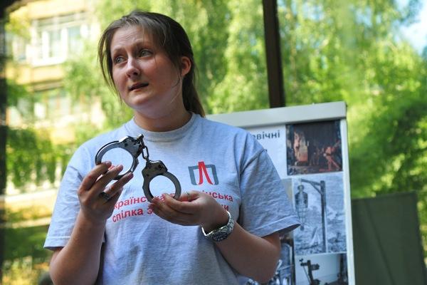 Участница акции, посвященной Международному дню против пыток, держит наручники, которыми в милиции пытают задержанных. Фото: Владимир Бородин/The Epoch Times