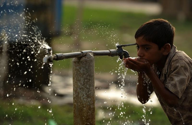 Индийский мальчик пьет воду из крана. Фото: DIPTENDU DUTTA/AFP/Getty Images