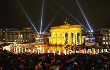 Глядачі дивляться на довге доміно, викладене з розмальованого пінопласту вздовж колишньої Берлінської стіни. Фото: Getty Images