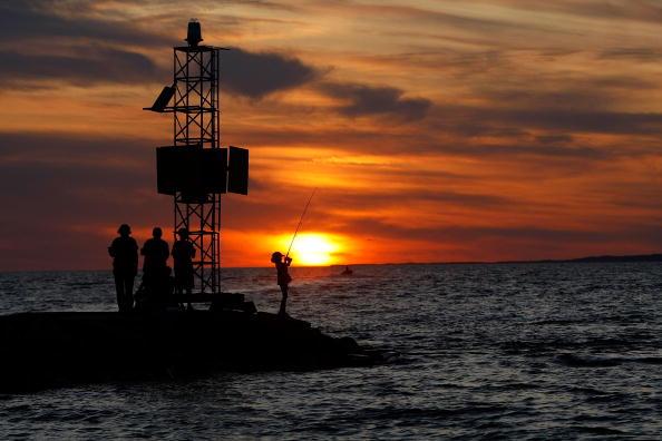 Девочка на закате ловит рыбу. Фото: Win McNamee/Getty Images