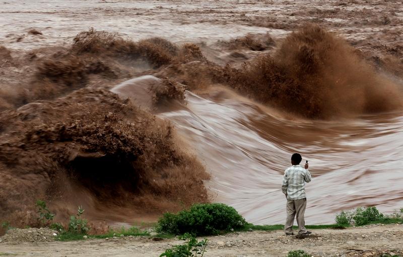 Штат Джамму, Індія, 4 серпня. Місцевий житель дивиться на високі хвилі в річці Таві, викликані сильними дощами. Фото: STRDEL/AFP/Getty Images