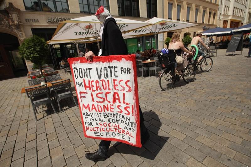 Берлін, Німеччина, 29 червня. Протестувальник у костюмі безголового банкіра закликає не підтримувати план Євросоюзу щодо виходу з кризи, вважаючи його божевільним. Фото: Sean Gallup/Getty Images