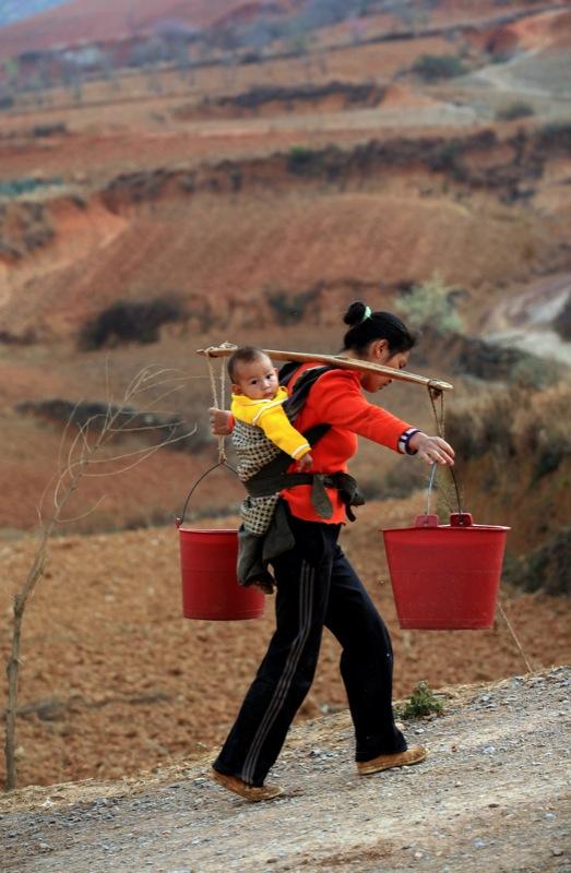 Китаянка, с ребенком на спине, несет ведра с водой, набранной в колодце, к себе домой в Yiliang, на юго-западе Китая в провинции Юньнань 27 февраля 2012 года. Засуха в провинции Юньнань оставила более 3 миллионов людей людей и 1,58 млн. голов скота, без н