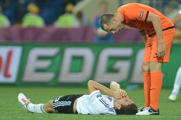 Голландский защитник Джон Хейтинга (справа) кричит в адрес немецкого форварда Марио Гомеса, который лежит на поле во время матча Нидерланды против Германии 13 июня 2012 года. Фото: PATRIK STOLLARZ/AFP/Getty Images