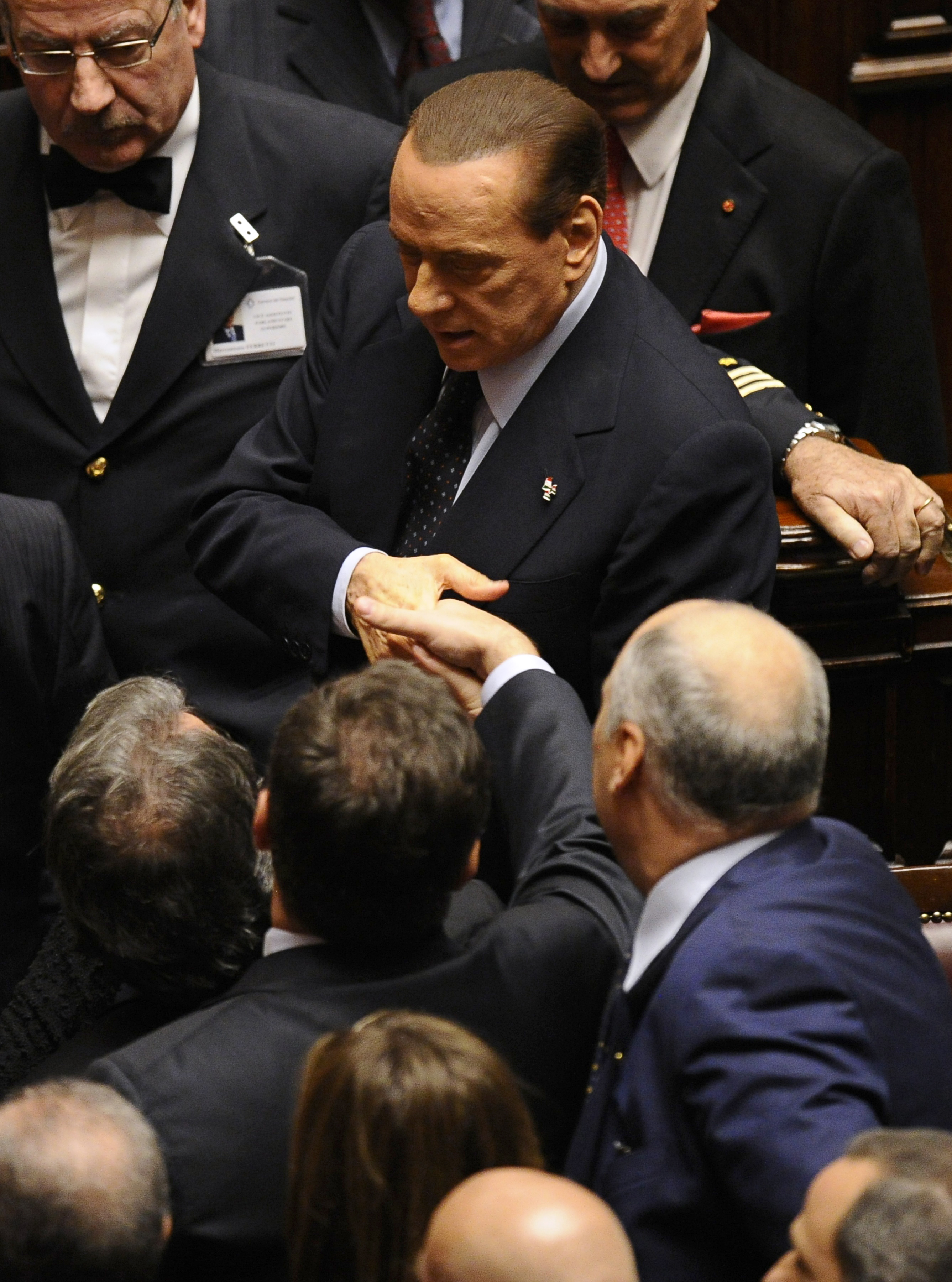 Прем'єр-міністр Італії Сильвіо Берлусконі потискує руки депутатам і міністрам за підсумками засідання парламенту щодо прийняття низки ключових економічних реформ. 12 листопада 2011 року, Рим. У той же день він пішов у відставку. Фото: Filippo Monteforte/G
