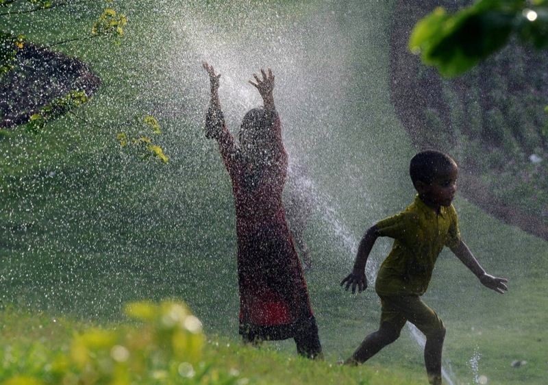 Пакистанские дети охлаждаются под брызгами воды. Фото: Arif Ali/AFP/Getty Images
