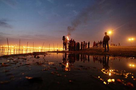 При свече огней и фонарей  паломники смотрят на Сангме, где проходят ритуальные купания. Аллахабад. Индия. (19.21.07)  Фото: Mario Tama/Getty Images