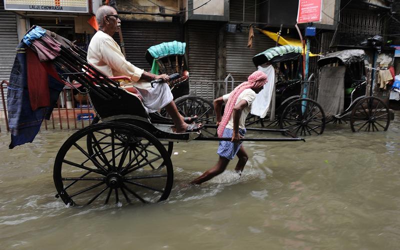 Калькутта, Индия, 30 июня. Непросто рикше выполнять свою работу во время сезона тропических дождей. Фото: DIBYANGSHU SARKAR/AFP/Getty Images