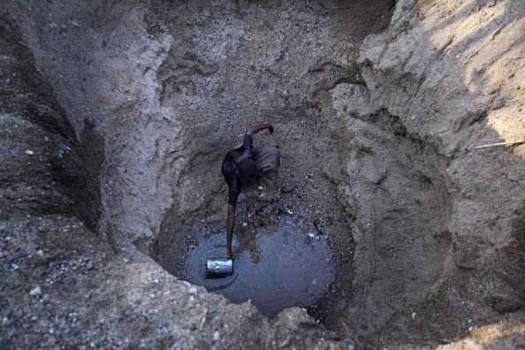 Юноши из отдаленного племени Теркана в северной части Кении откопали яму и пытаются извлечь воду из высохшего русла реки. Фото: Christopher Furlong/Getty Images